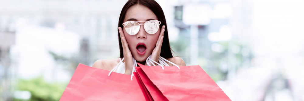 Woman holding shopping bags who is surprised for holiday shopping.
